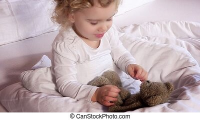 Lovely little girl kiss her best friend loved teddy bear toy...