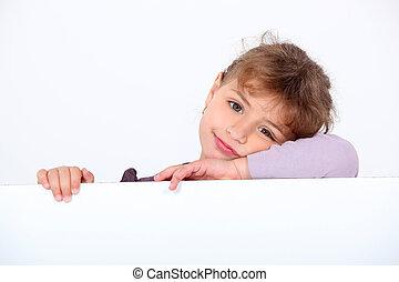 Lovely little girl leaning on a white panel