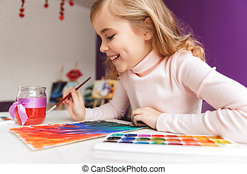 Lovely little girl painting a picture at the table