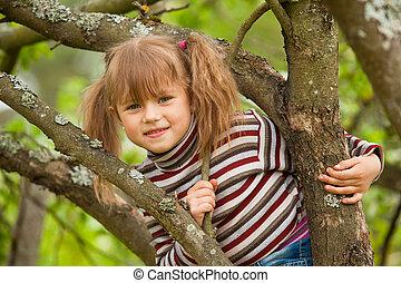 Lovely little girl posing sitting on a tree in the garden.