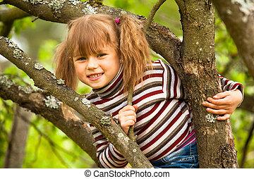 Lovely little girl posing sitting on a tree in the garden