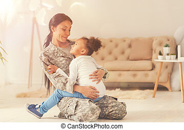 Lovely little girl sitting in the lap of her mother-soldier