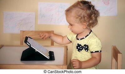 Lovely little girl using tablet computer sitting near table.