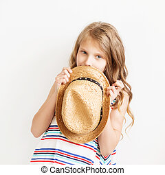 Lovely little girl with straw hat against a white background.