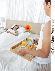 Lovely man bringing the breakfast to his girlfriend lying on the bed at home