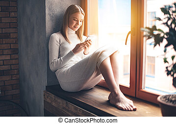 Lovely message. Beautiful young woman using her smartphone...
