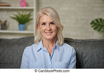 Lovely middle aged blond woman with a beaming smile sitting on a sofa at home