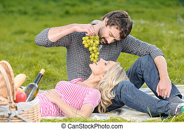 Lovely moments. Young men feeding his girlfriend with a grapes bunch on the picnic