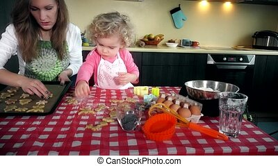 Lovely mother and daughter place cookies biscuits to oven plate tin in kitchen