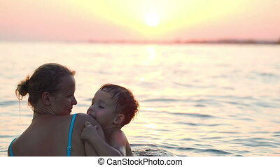 Lovely mother and little son swimming in sea