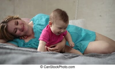 Lovely mother playing with newborn child in bed