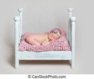Lovely newborn baby girl sleeps on the crib