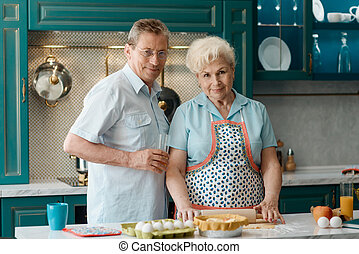 Lovely old couple posing for a photo in kitchen