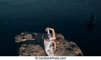 Lovely oriental dancer girl performing a dance on one of mountains near the sea in Crimea