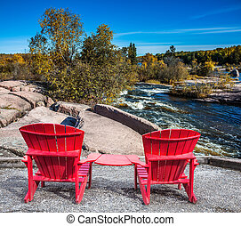 Lovely place to relax. Two red beach chairs on the riverbank. Winnipeg River, Old Pinawa Dam Park. The concept of ecological and recreational tourism
