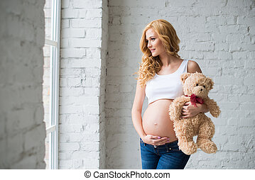 Lovely pregnant girl with a teddy bear.