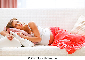 Lovely pregnant woman sleeping on sofa