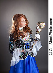 Lovely red-haired girl posing with masquerade mask -...
