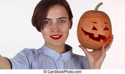 Lovely red lipped woman taking selfies with carved Halloween pumpkin
