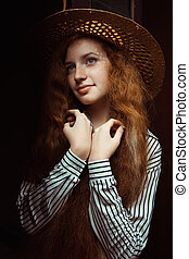 Lovely redhead model with long curly hair in straw hat posing near the old door