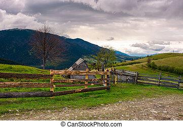 lovely rural landscape in Carpathians. wooden fence along...