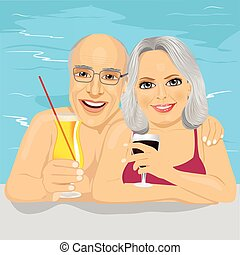 lovely senior couple drinking red wine and cocktail in pool