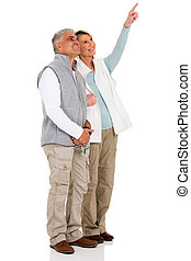 senior couple pointing at empty copy space