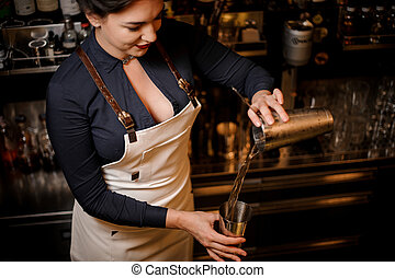Lovely sexy smiling barmaid making a fresh summer cocktail -...