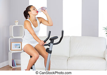 Lovely slender woman drinking while training on an exercise bike in her living room at home
