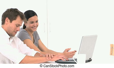 Lovely smiling couple searching something on their laptop