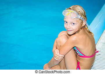 lovely smiling girl in the swimming pool