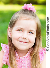 Lovely smiling little girl with long blond hair, closeup outdoor portrait, summer day in park