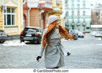 Lovely smiling red haired girl wearing stylish winter outfit walking in city, spinning around. Empty space