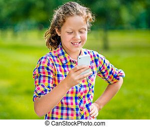 Lovely smiling teenage girl in casual clothes with smartphone in her hand, looking at screen, reading a message, using Facebook in sunny day in summer park
