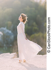 Lovely smiling young blonde bride standing in the top of hill on nature with flowing white dress