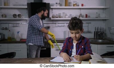 Lovely son doing homework while dad mopping floor -...