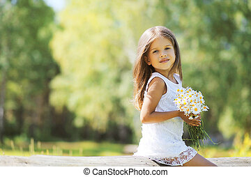 Lovely spring girl with flowers on nature in sunny day