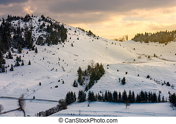 yellow glowing sky above the snow covered hill - lovely...