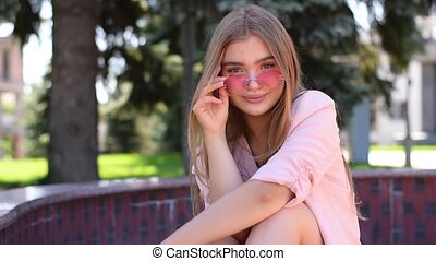 Lovely teenage girl with straight long blonde hair sitting...