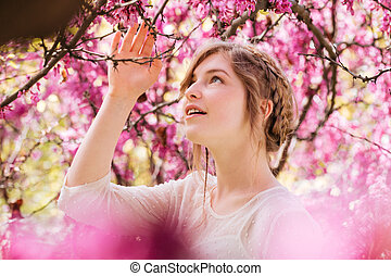Lovely tender young woman in spring garden with blooming...
