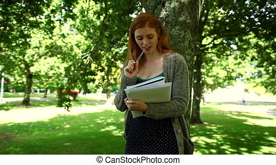 Lovely thinking redhead doing assignments standing in park...