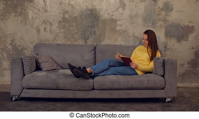 Lovely tired girl with book taking a nap on sofa