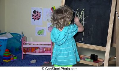 lovely toddler girl drawing on chalkboard at home