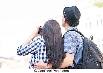 Lovely tourist couple making photos