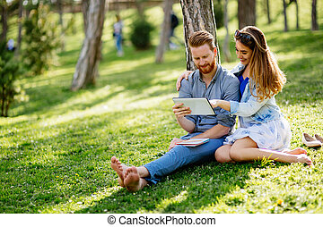 Lovely university students studying outdoors in park
