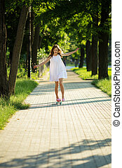 Young girl riding in the park on a skateboard