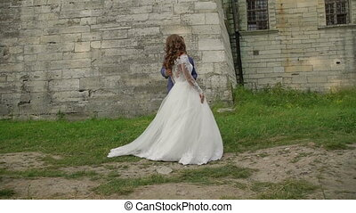 Lovely wedding couple coming to each other and embraces at castle. Slowly