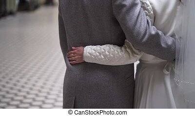 Lovely wedding couple embracing and holding hands