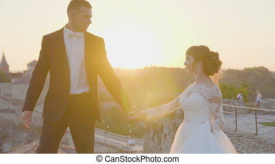 Lovely wedding couple kisses each other and embraces near the castle sunset 4k