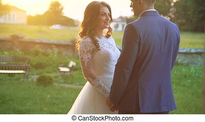 Lovely wedding couple kisses each other and embraces near the castle. Slowly